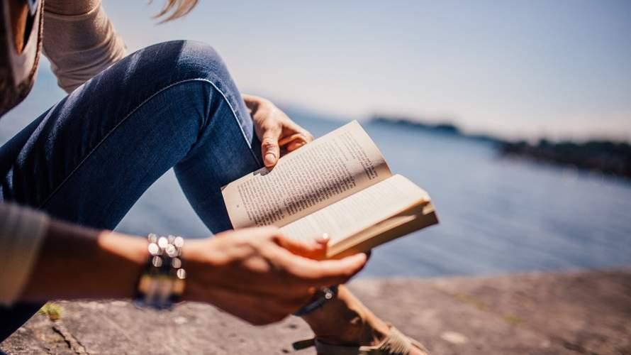 žena, ktorá číta knihu a brehu rieky